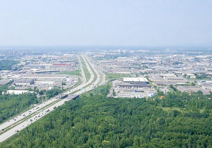Photographie aérienne en couleur. Vue sur l'autoroute Jean-Noël Lavoie et le secteur industriel de Laval.