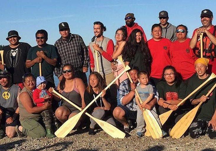 Groupe d'hommes et de femmes souriants tenant des pagaies de canots