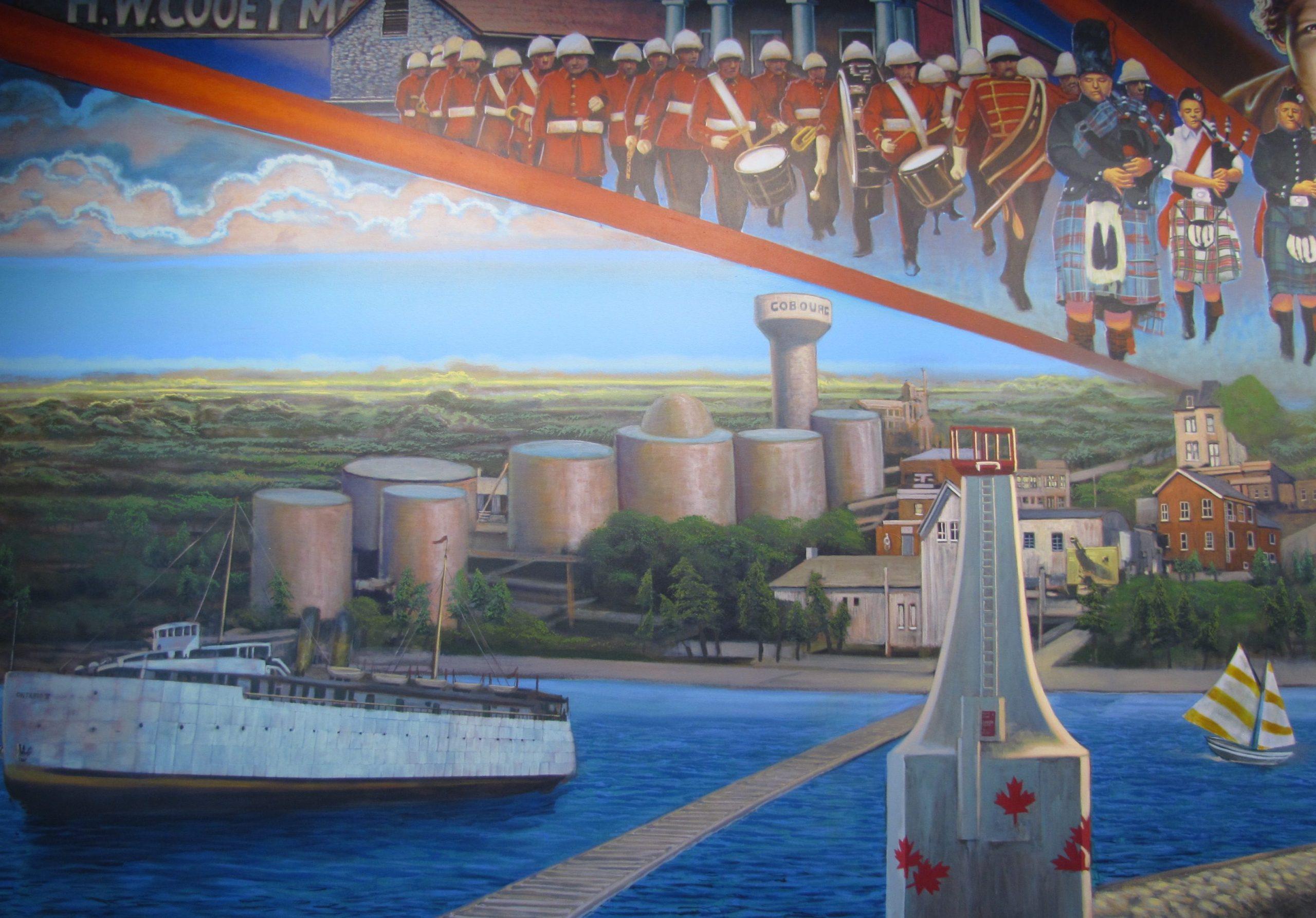 Une peinture murale aux multiples couleurs illustrant, à droite, le phare blanc actuel de Cobourg et, à gauche, un grand transbordeur, blanc lui aussi. Sur la rive, un peu en retrait vers la gauche, sept grands réservoirs à pétrole couleur argent et un réservoir d'eau surélevé. À droite, derrière le phare, il y a quelques entreprises. L'harmonie de Cobourg, habillée en uniforme rouge, et le corps de cornemuses de la légion, en kilts variés, défilant en formation militaire, sont dépeints au-dessus des nuages.