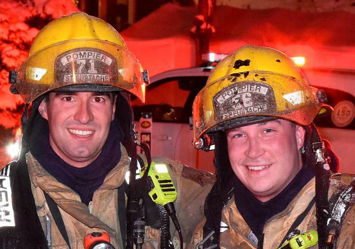 Photographie de deux pompiers souriants en tenue de combat contre le feu, devant un camion de pompiers, une voiture et plusieurs maisons lors d'une nuit éclairée.