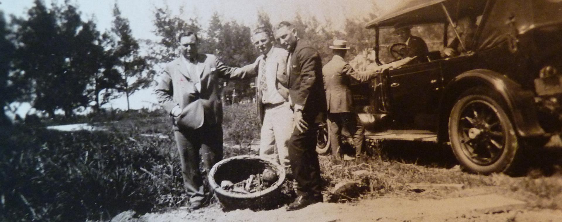 Trois hommes prennent la pose devant une automobile de l'époque.