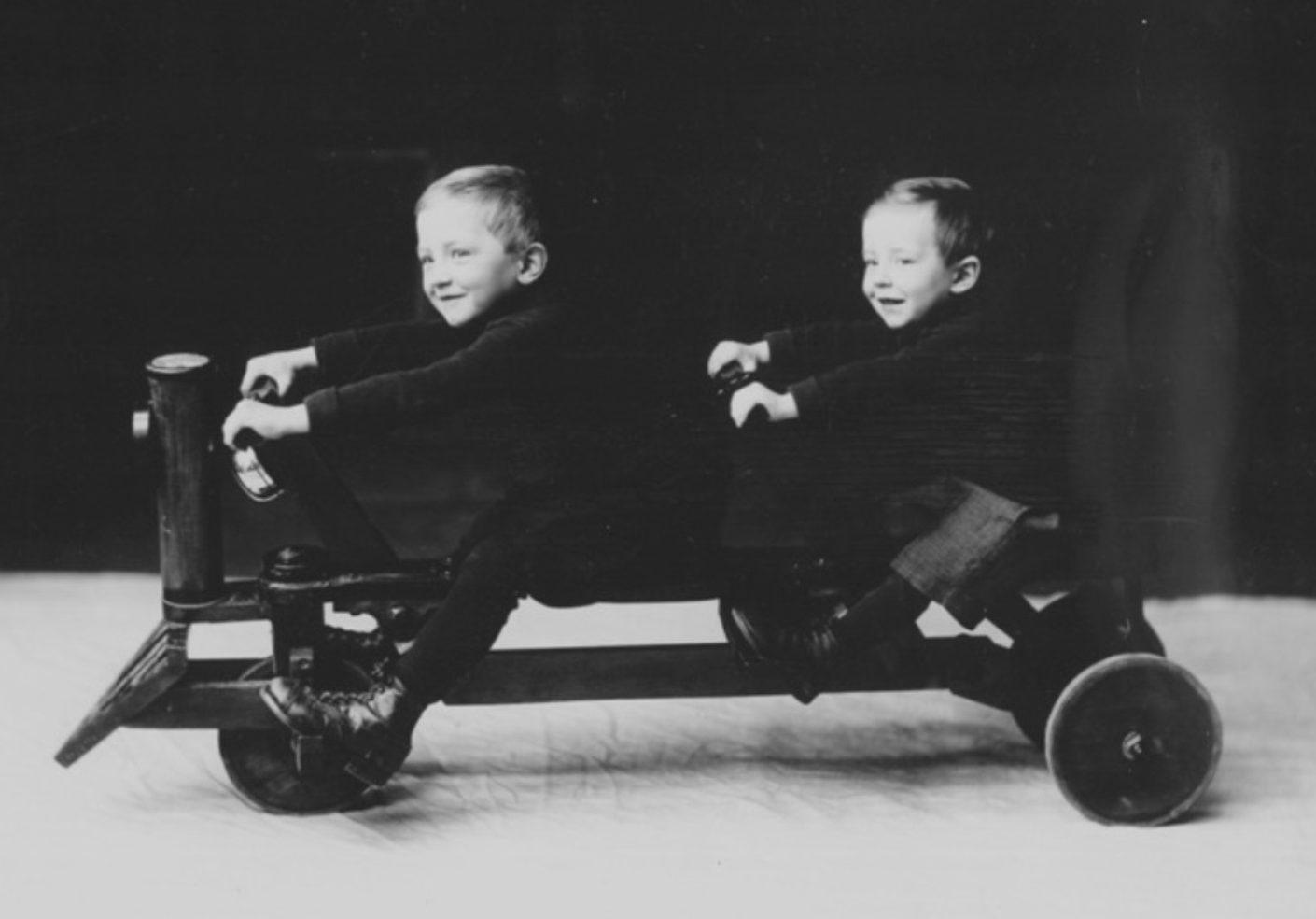Photo ancienne noir et blanc avec 2 petits enfants souriants assis sur une voiturette à 3 roues avec 2 guidons.