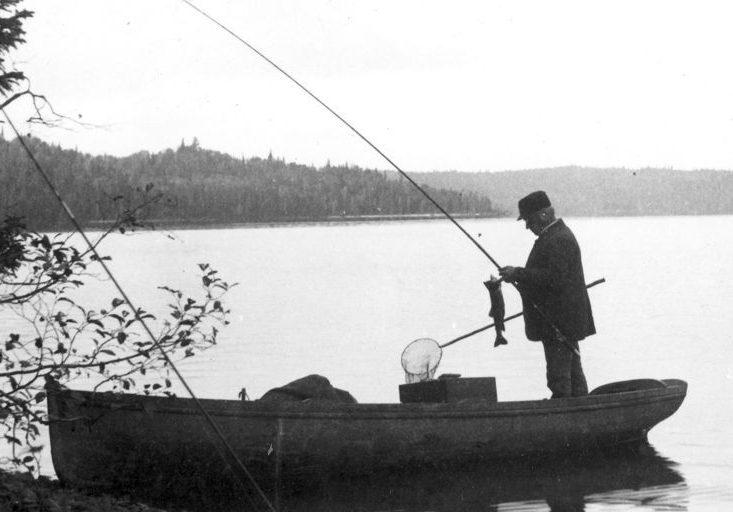 Photo en noir et blanc de pêcheurs dans un bateau à vapeur sur le lac Édouard. Au premier plan, un bateau au bord de la rivière; dedans se tient un homme décrochant un poisson de sa canne.