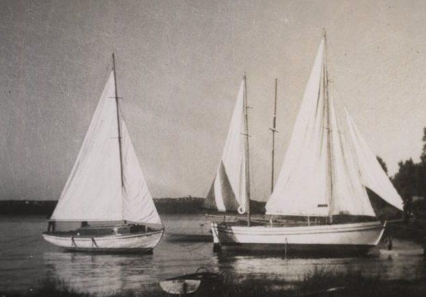 Photographie noir et blanc de trois yachts blancs, aux voiles hissées, ancrés près de la rive
