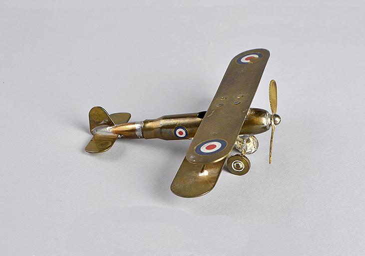 Petit avion en laiton lustré fait avec une cartouche de carabine. L'avion possède une hélice à l'avant et des cocardes sur chaque aile et sur le fuselage.