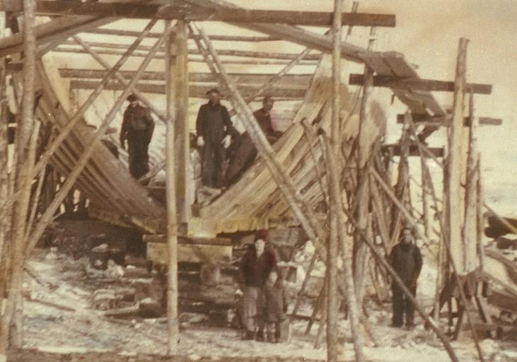 Vue d'une goélette en construction. On y voit la charpente du bateau entourée par des échafaudages.