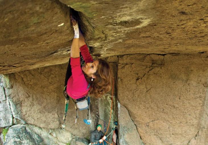 Plan rapproché d'une femme accrochée par les mains et les pieds sous un toit de roche d'environ 15 mètres d'avancé.