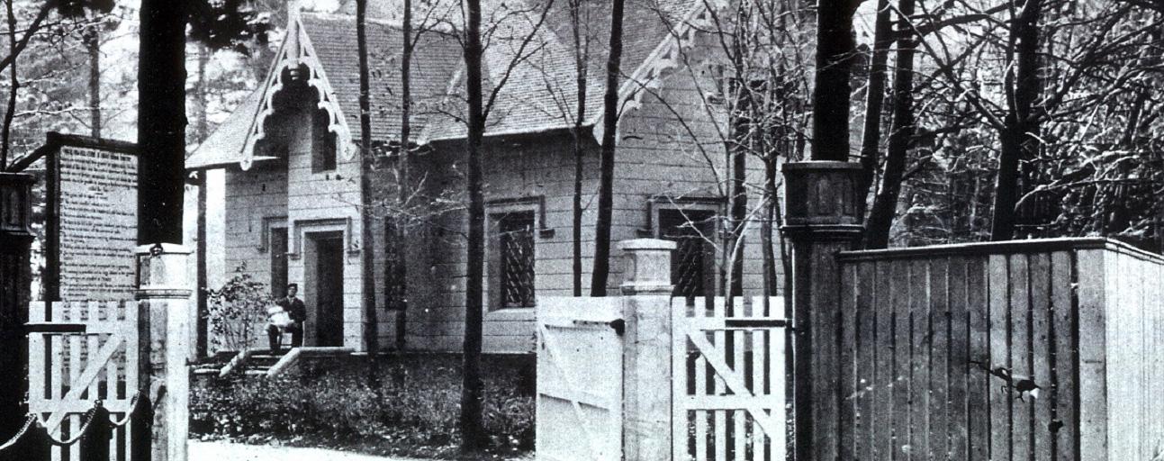 Photo noir et blanc d'une maison entourée d'arbres. Un homme est assis sur le perron tenant un bébé. A l'avant-plan une grande clôture avec une large barrière de bois ouverte.