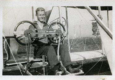 Un homme assis aux commandes d'un biplan d'entraînement.