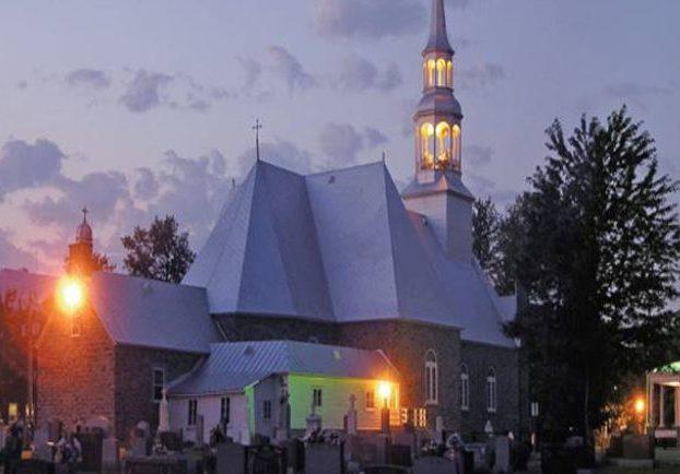 Photographie couleur prise de nuit, plan éloigné de l'arrière des bâtiments comprenant l'église, le presbytère et le cimetière, l'église est éclairée.