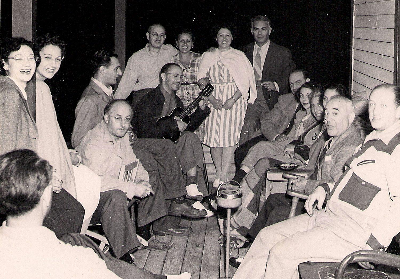 Seize hommes et femmes assis sur une véranda en bois. Un des hommes tient un ukulélé.
