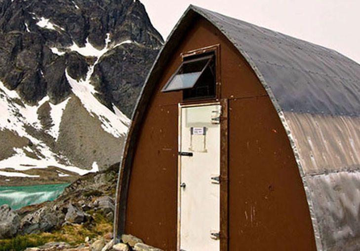 Entrée principale du refuge voûté de style gothique avec sa paroi d'extrémité brune et sa porte blanc brillant, près de l'eau turquoise du lac glaciaire. En arrière-plan, surgit un sommet sombre recouvert de couches de neige éparses.