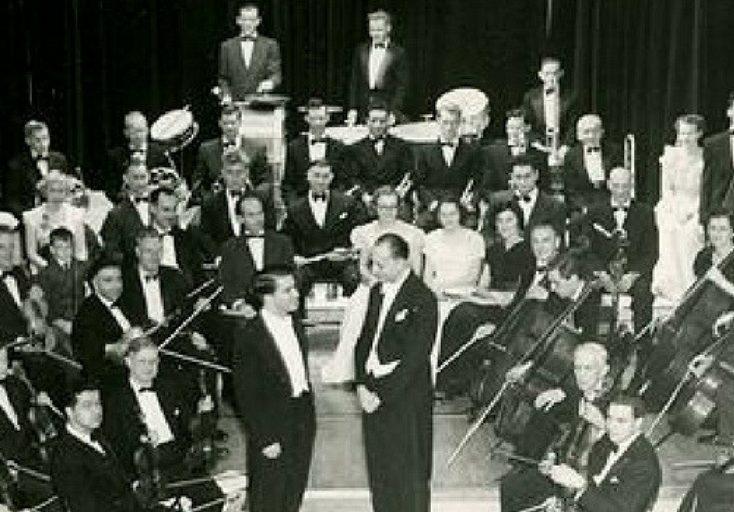 L'artiste invité et le chef s'interposent au centre de la photo avec l'orchestre qui s'assoit durant la répétition en costume
