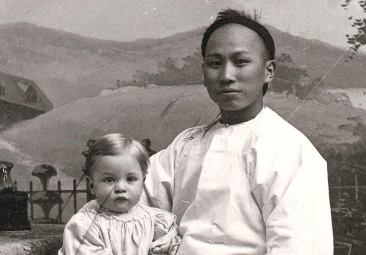 Employé de maison chinois posant pour un photographe, assis sur une chaise avec un jeune enfant sur le genou droit