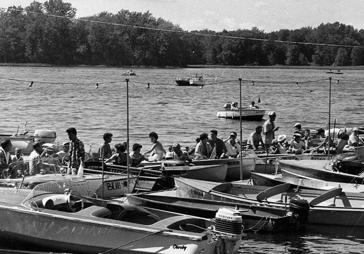 Photographie en noir et blanc de petits bateaux à moteur amarrés à un quai. Plusieurs personnes sont installées dans leur embarcation, prêtes pour le départ d'une parade nautique.