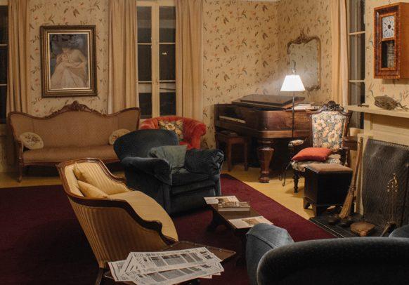 Salon de la résidence d'été avec deux canapés, deux fauteuils, un piano et un foyer.