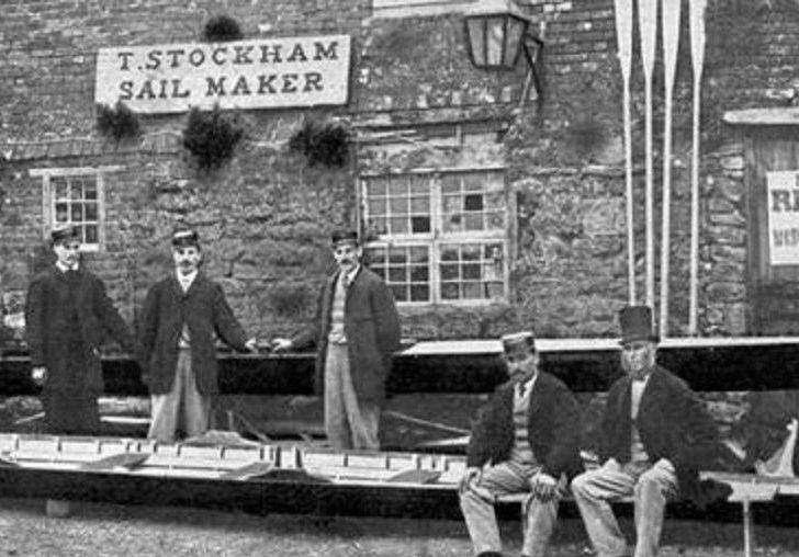 Image des membres de l'équipage de Paris avec leur gérant, J. A. Harding, posant devant un hangar à bateaux à leur arrivée à Southampton, en Angleterre. Cette photographie en noir en blanc datant de juillet 1867 montre un bâtiment fait de blocs de pierre. Leur aviron est devant le bâtiment, les rames appuyées contre la façade.