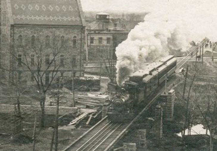 Photographie montrant un train circulant sur la voie ferrée et l'hôtel de ville d'Almonte à l'arrière-plan, années 1950