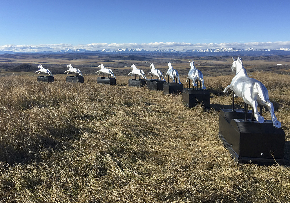 Photo couleur d'un paysage avec huit chevaux mécaniques à pièces alignés devant le panorama de la montagne
