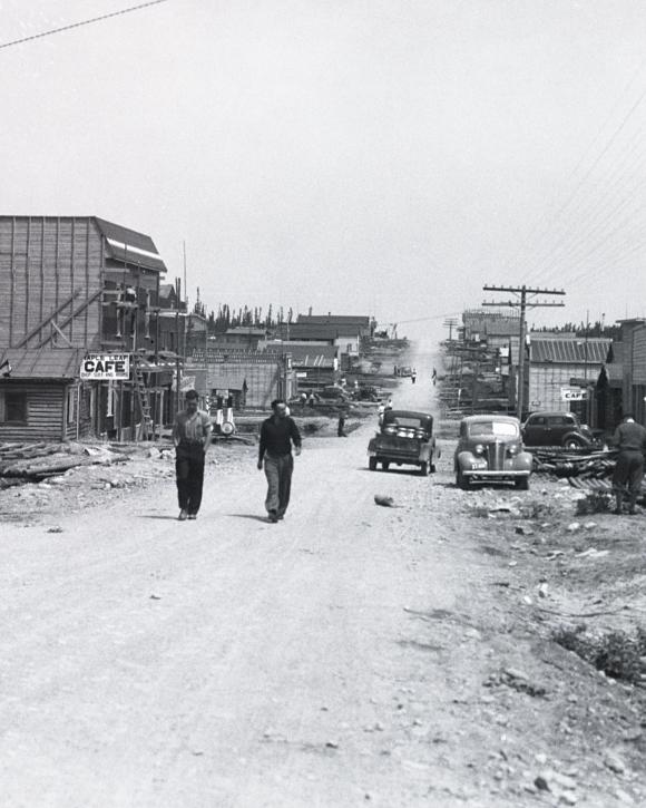 Photographie en noir et blanc d'une route de gravier bordée de bâtiments de planches ou en bois rond. Deux hommes marchent vers la caméra.