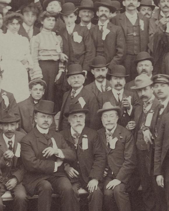 Photographie sépia illustrant des hommes et quelques femmes à l'extérieur devant une usine.