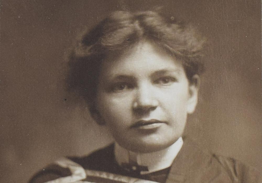 Photographie en noir et blanc de Maude Abbott, jeune adulte, de la taille à la tête. Elle porte un habit et une toge de graduation. Ses cheveux foncés sont attachés à l'arrière de sa tête et sa tête est légèrement tournée vers la gauche.