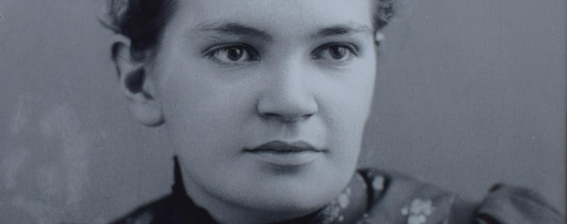 Photographie montrant le visage de la docteure Maude Elizabeth Abbott en gros plan panoramique. Elle est jeune et porte une robe à fleur. Son regard est perçant. Elle sourit paisiblement. Elle a 22 ans.