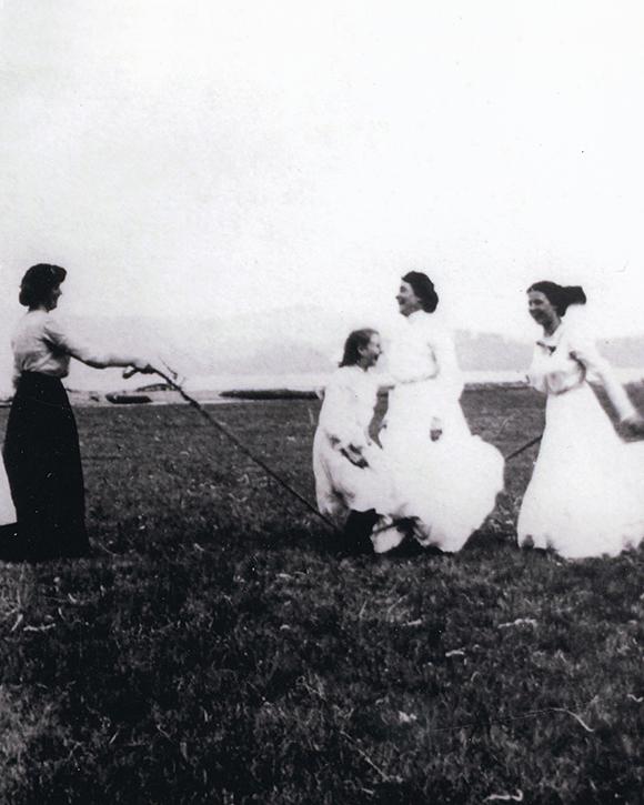 Une photographie noir et blanc des femmes jouent à la corde à sauter dans un camp.